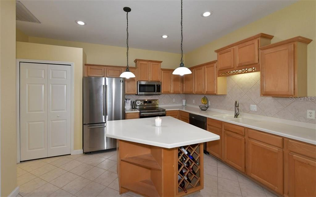 Kitchen has wood cabinets, corian countertops, stainless appliances, closet pantry. - Villa for sale at 4812 Lakescene Pl, Sarasota, FL 34243 - MLS Number is A4486070