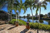 Lush tropical foliage and direct water views from pavered and open patio area. - Single Family Home for sale at 5281 Cape Leyte Way, Sarasota, FL 34242 - MLS Number is A4171478