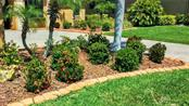 Landscaping with stones for mulch bed and cobble edging - Single Family Home for sale at 7658 Trillium Blvd, Sarasota, FL 34241 - MLS Number is A4182608