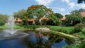 View of the carriage house & flame tree from across the lake - Condo for sale at 1742 Landings Blvd #38, Sarasota, FL 34231 - MLS Number is A4439252