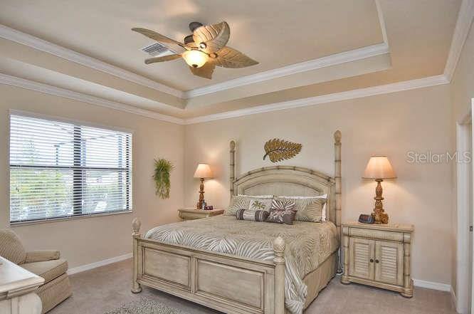 Master bedroom with tray ceiling accented with crown molding - Single Family Home for sale at 13210 Amerigo Ln, Venice, FL 34293 - MLS Number is N5913012