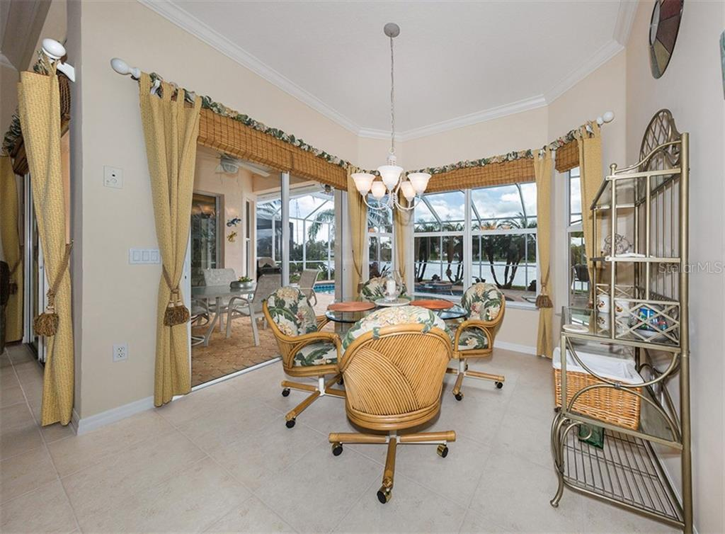 Dinette with slides to lanai and view of lake - Single Family Home for sale at 627 Lakescene Dr, Venice, FL 34293 - MLS Number is N6103268