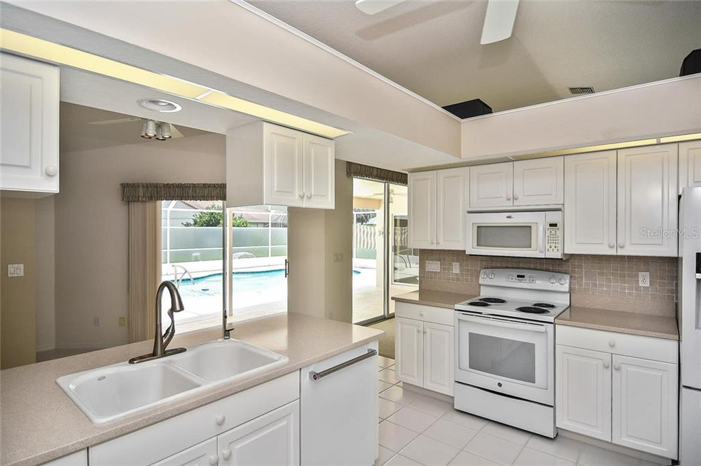 Kitchen with pool view - Single Family Home for sale at 2232 E Village Cir, Venice, FL 34293 - MLS Number is N6105697