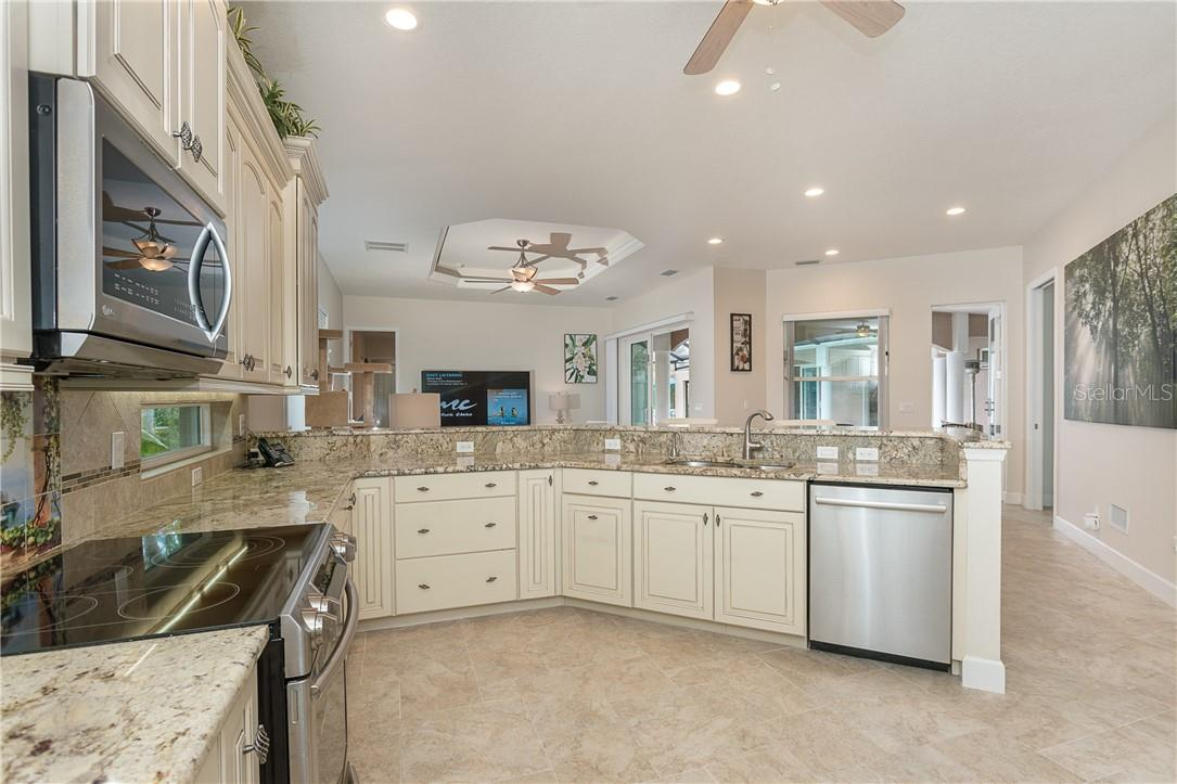 From the kitchen, overlooking family room and courtyard beyond. - Single Family Home for sale at 1670 Maria St, Englewood, FL 34223 - MLS Number is N6113779