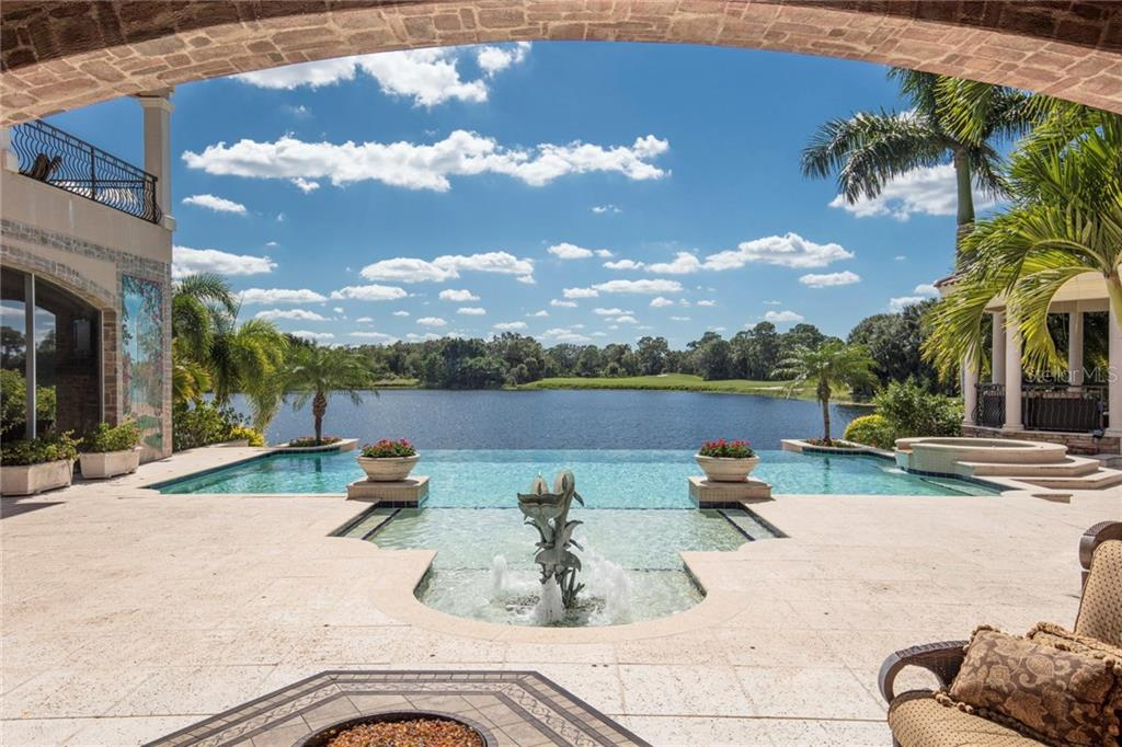 Few residences in all of University Park, even Sarasota, offer a lakefront setting as vast and all-encompassing as this! - Single Family Home for sale at 7320 Barclay Ct, University Park, FL 34201 - MLS Number is A4200908
