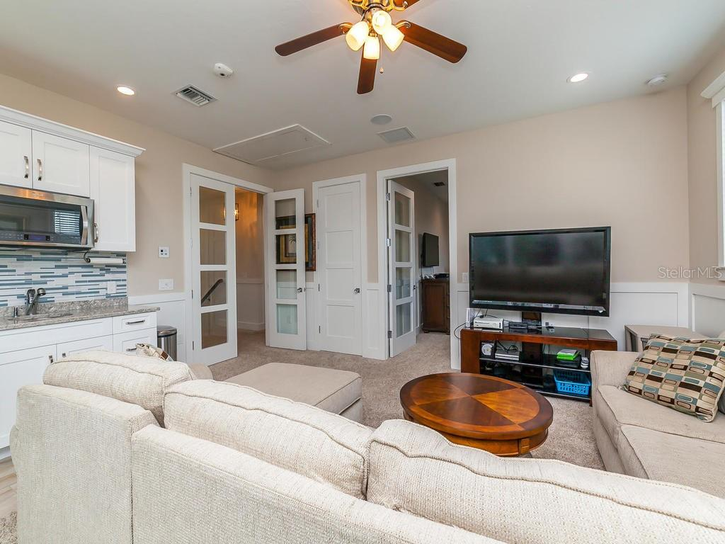 Family room with kitchenette and adjacent to media room - Single Family Home for sale at 7643 Cove Ter, Sarasota, FL 34231 - MLS Number is A4403215