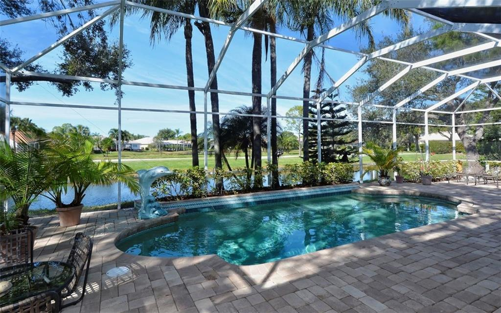 Tranquil water views from the paver'd oversized lanai and heated pool. - Single Family Home for sale at 8926 Grey Oaks Ave, Sarasota, FL 34238 - MLS Number is A4425574
