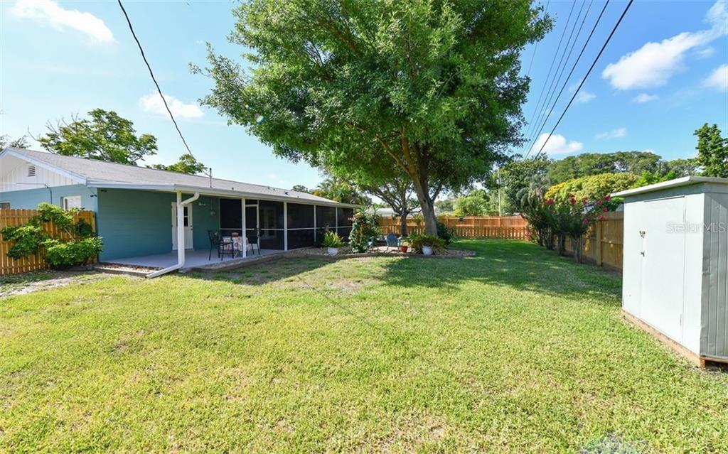 Large fenced backyard with shade tree and storage shed. - Single Family Home for sale at 120 23rd Street Ct Ne, Bradenton, FL 34208 - MLS Number is A4438232