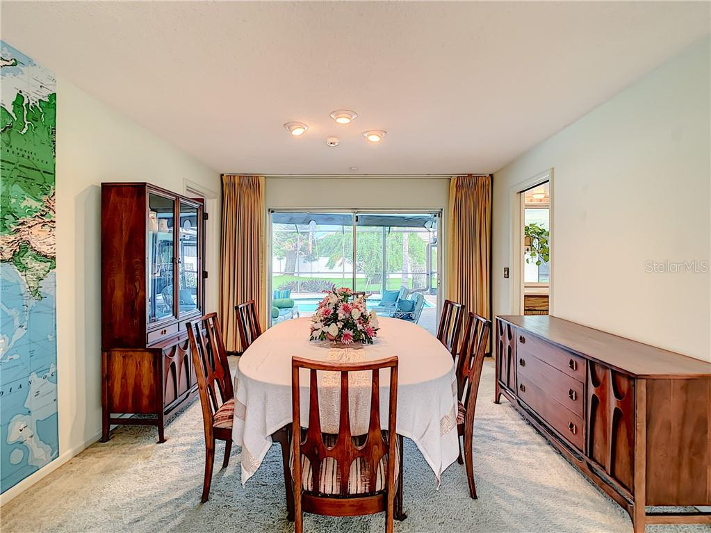 Dining room looking towards pool and lanai.  Master bedroom is on the left. - Single Family Home for sale at 7006 18th Ave W, Bradenton, FL 34209 - MLS Number is A4450658