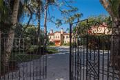 Gated entry - new shell circular drive - separate gated exit on other side of circular drive - view to main house with guest quarters, garage, and separate office/studio on the right - Single Family Home for sale at 3221 Bay Shore Rd, Sarasota, FL 34234 - MLS Number is A4200323